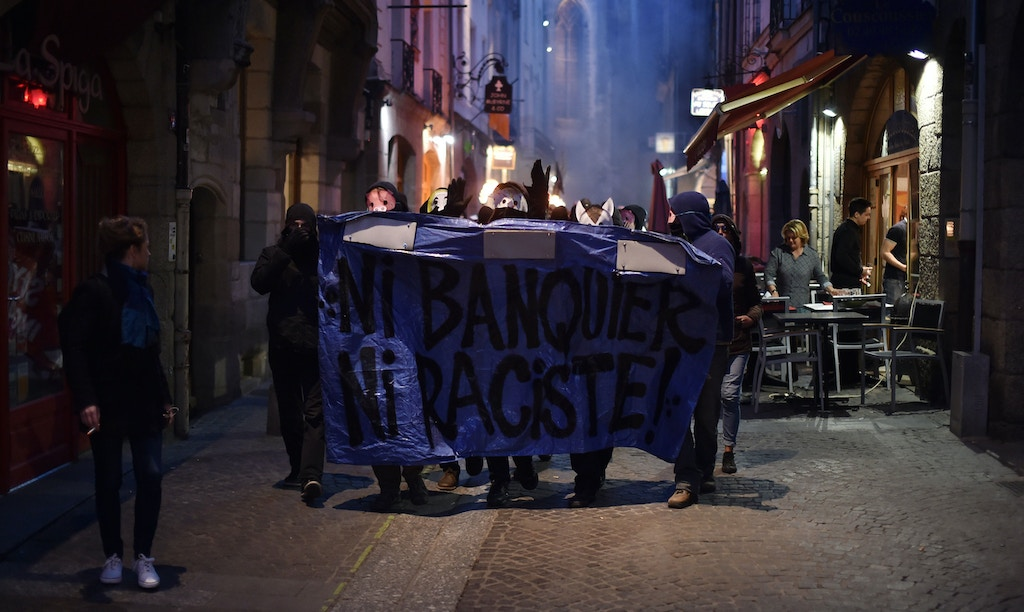 "Anti-fascists march behind a banner reading ""no banker, no racist"" demonstrate in Nantes, western France, on April 23, 2017 following the announcement of the results of the first round of the Presidential election.<br /> Centrist Emmanuel Macron finished ahead of far-right leader Marine Le Pen on April 23, 2017 to qualify alongside her for the runoff in France's presidential election, initial projections suggested.  / AFP PHOTO / JEAN-SEBASTIEN EVRARD        (Photo credit should read JEAN-SEBASTIEN EVRARD/AFP/Getty Images)"