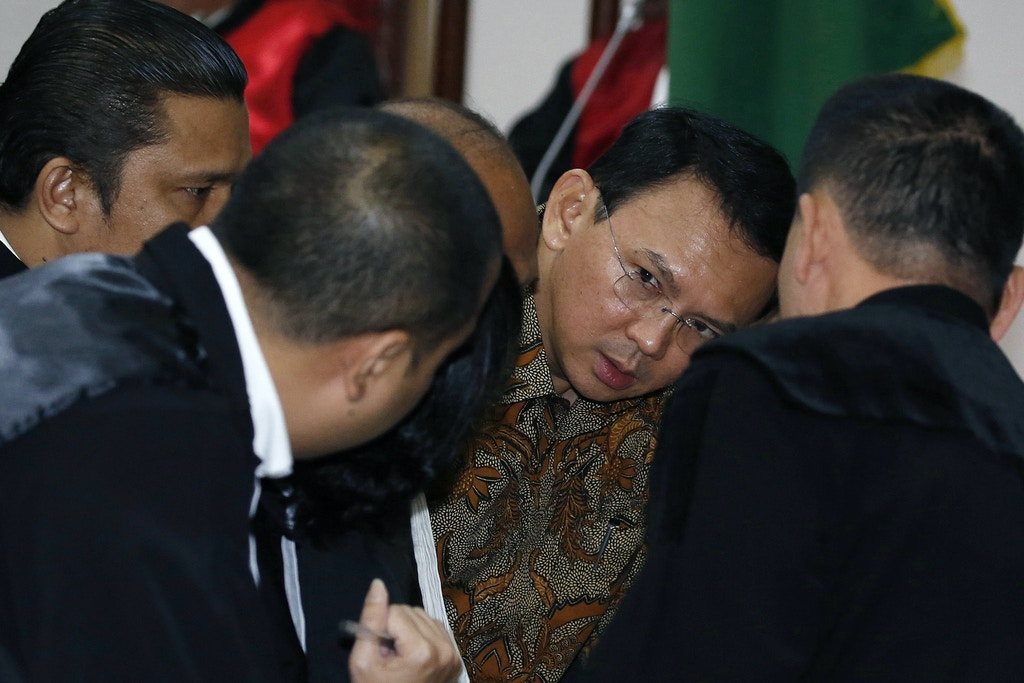 Jakarta's Governor Basuki Tjahaja Purnama, also known as Ahok speaks to his lawyers inside the courtroom during his blasphemy trial at the auditorium of the Agriculture Ministry in Jakarta on April 11, 2017. The first Christian to govern the capital in more than 50 years, Purnama is on trial accused of blasphemy over remarks he made about the Koran. / AFP PHOTO / POOL / Beawiharta (Photo credit should read BEAWIHARTA/AFP/Getty Images)