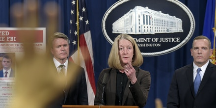 Acting Assistant Attorney General Mary McCord, center, accompanied by U.S. Attorney for the Northern District Brian Stretch, left, and FBI Executive Director Paul Abbate, calls on a reporter during a news conference at the Justice Department in Washington, Wednesday, March 15, 2017. The Justice Department announced charges against four defendants, including two officers of Russian security services, for a mega data breach at Yahoo. (AP Photo/Susan Walsh)