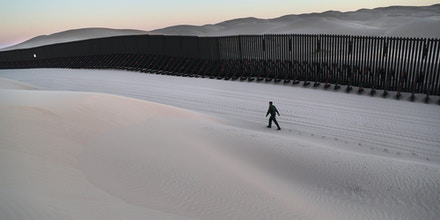 FELICITY, CA - NOVEMBER 17:  A U.S. Border Patrol agent walks along the U.S.-Mexico border at the Imperial Sand Dunes on November 17, 2016 near Felicity, California. The 15-foot border fence, also known as the