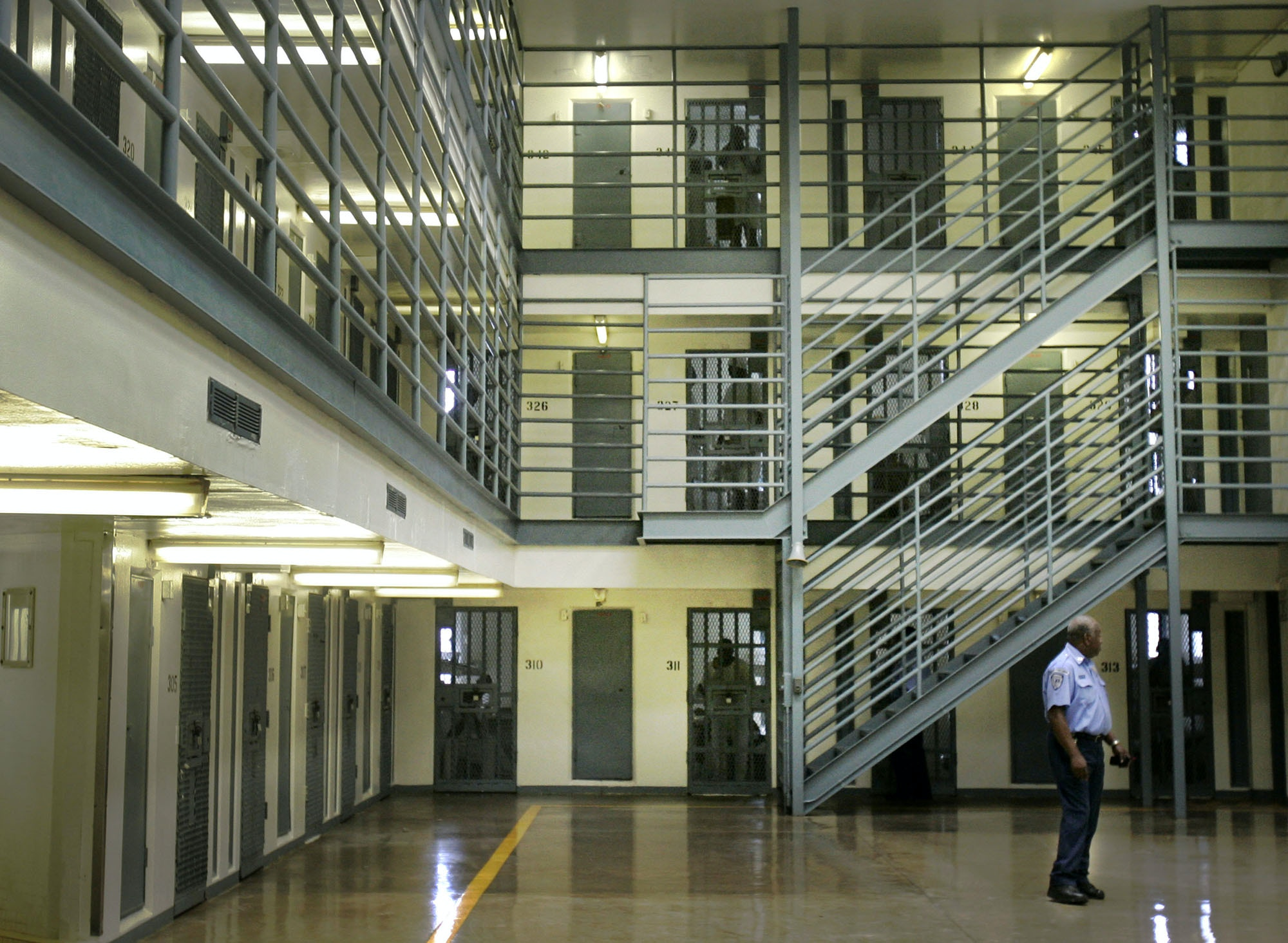 In this photo taken Monday, Aug. 10, 2009, an Arkansas Department of Correction officer patrols a cell block at the agency's Cummins Unit near Varner, Ark. (AP Photo/Danny Johnston)