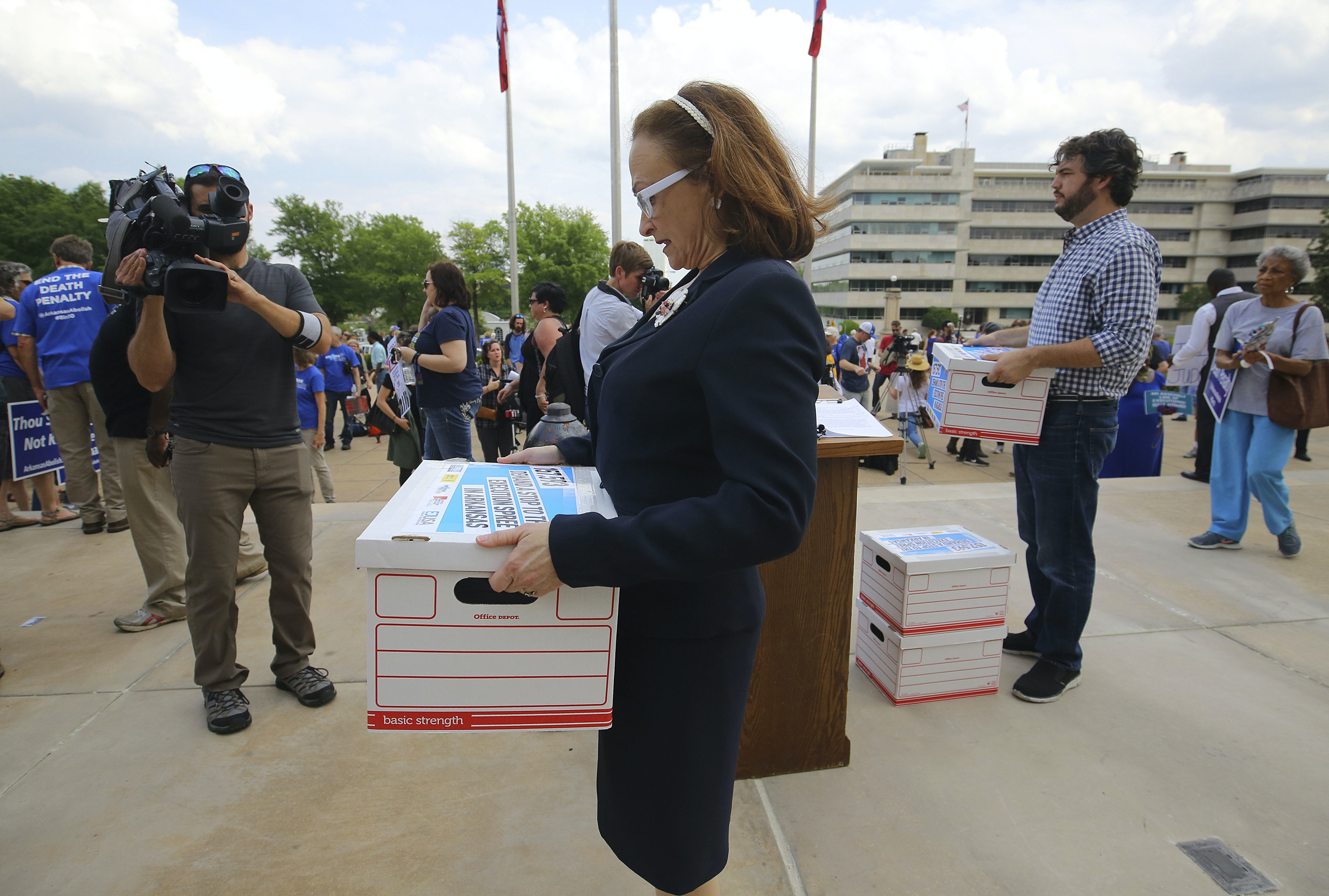 Arkansas American Civil Liberties Union executive director Rita Sklar and others prepare to carry boxes containing petitions to Gov. Asa Hutchinson's office asking him to stay upcoming executions following a rally opposing the executions, on the front steps of Arkansas' Capitol, Friday, April 14, 2017, in Little Rock, Ark. (Stephen B. Thornton/The Arkansas Democrat-Gazette via AP)