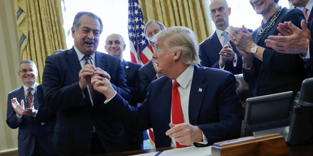 President Donald Trump gives the pen he used to sign an executive order to Dow Chemical President, Chairman and CEO Andrew Liveris, as other business leaders applaud in the Oval Office of the White House in Washington, Friday, Feb. 24, 2017. The executive order would establish regulatory reform officers and task forces within federal agencies a part of his push to slash federal government regulations. (AP Photo/Pablo Martinez Monsivais)
