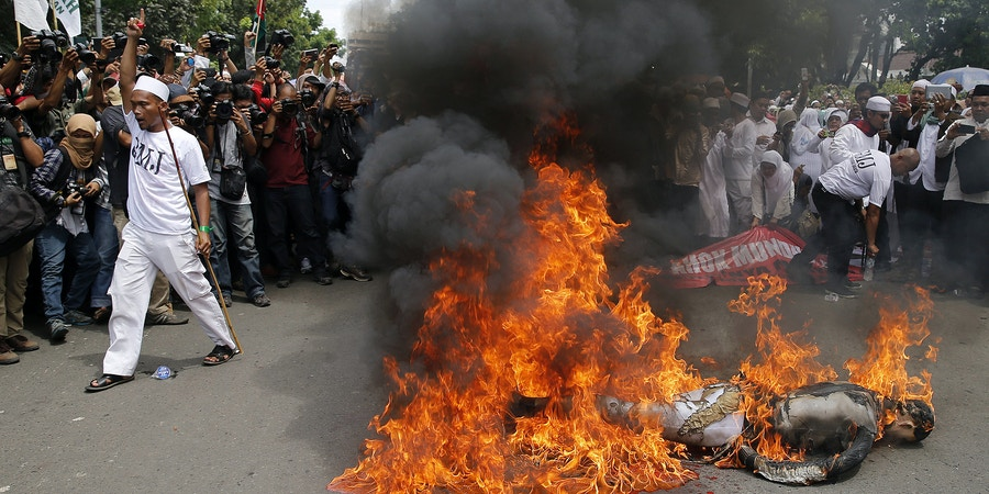 A member of the hardline Islamic group, the Islamic Defenders Front (FPI) shouts slogans after burning an effigy of Jakarta Governor Basuki Tjahaja Purnama or Ahok as they reject Ahok as their governor in front of Jakarta's city hall, December 1, 2014. Jakarta's first Christian governor in nearly 50 years was sworn in two weeks ago, despite protests from religious hardliners opposing a non-Muslim taking over one of Indonesia's most powerful political jobs. REUTERS/Beawiharta (INDONESIA - Tags: POLITICS CIVIL UNREST) - RTR4G75L