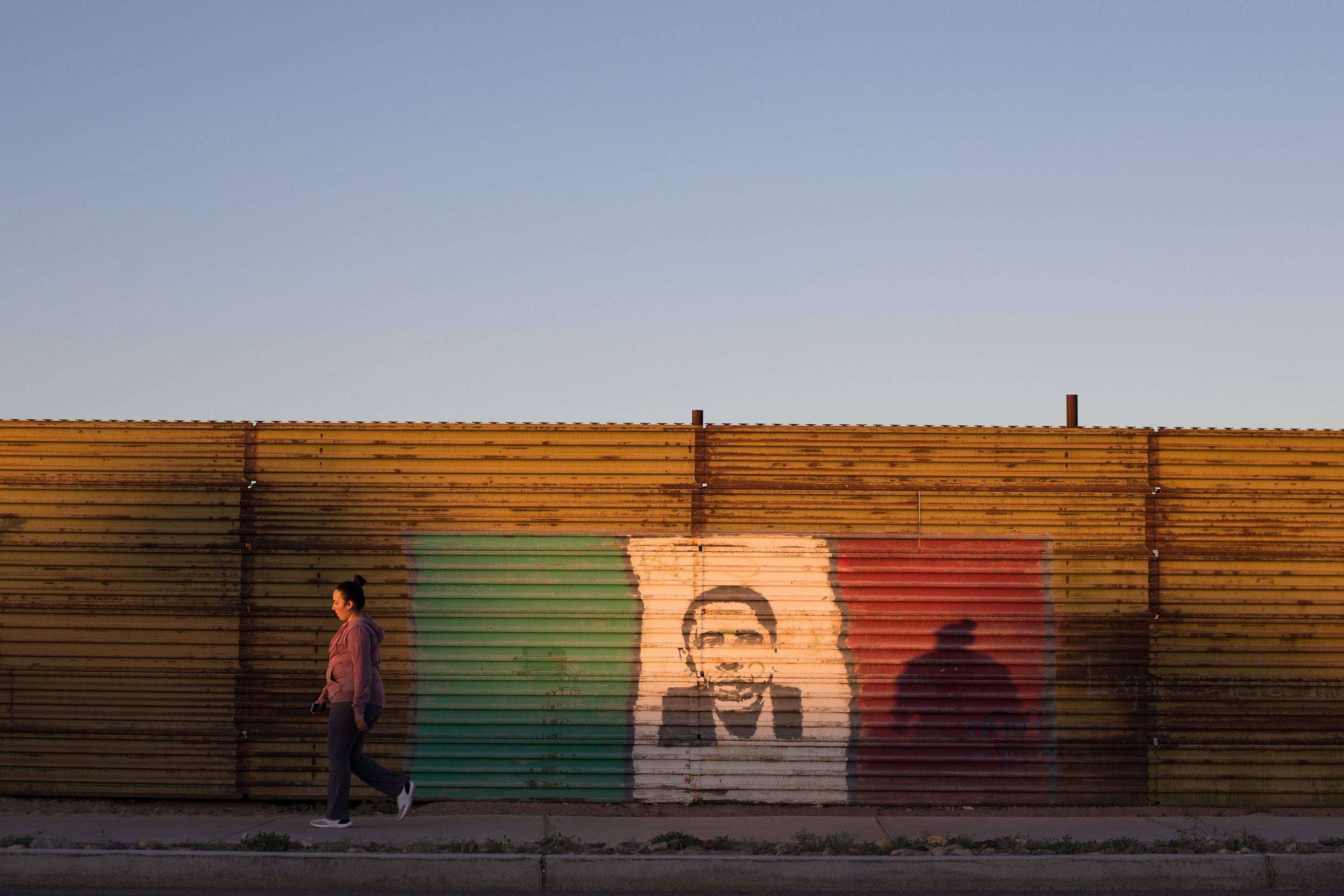 TOPSHOT - A woman walks next to a painting of former US President Barack Obama at the US/Mexico border fence in San Luis Rio Colorado, Sonora state, on February 15, 2017, northwestern Mexico. Attention Editors, this image is part of an ongoing AFP photo project documenting the life on the two sides of the US/Mexico border simultaneously by two photographers traveling for ten days from California to Texas on the US side and from Baja California to Tamaulipas on the Mexican side between February 13 and 22, 2017. You can find all the images with the keyword : BORDERPROJECT2017 on our wire and on www.afpforum.com / AFP / GUILLERMO ARIAS (Photo credit should read GUILLERMO ARIAS/AFP/Getty Images)