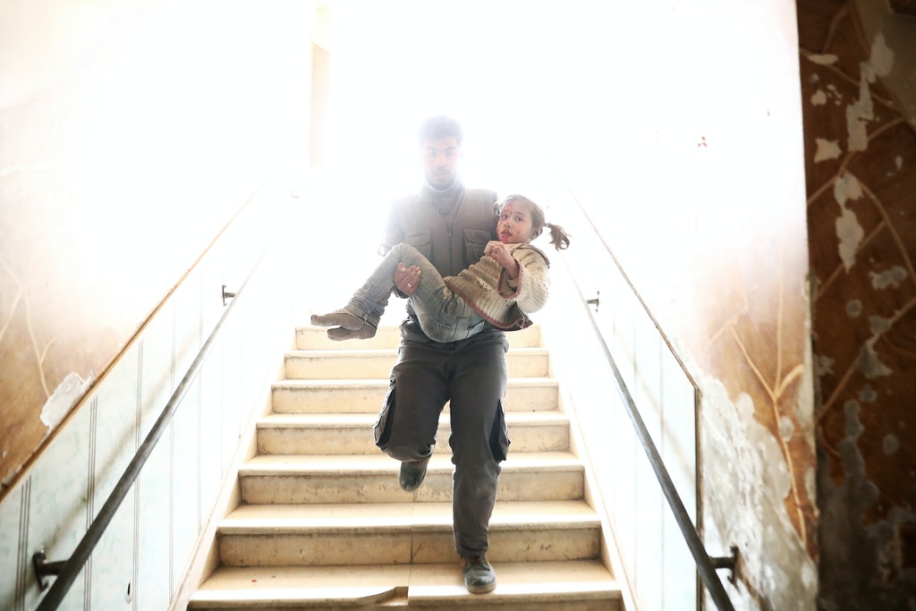 TOPSHOT - A Syrian civil defence volunteer carries a wounded girl as he rushes to a make-shift hospital following reported government airstrike on the rebel-held town of Douma, on the eastern outskirts of the capital Damascus, on February 25, 2017.<br /><br /><br /> Syrian regime forces carried out raids on several areas in the country, targeting mainly the besieged town of Douma, causing the deaths of at least 13 civilians, according to Syrian Observatory for Human Rights. The raids continued despite the United Nations confirmation a few days earlier that Moscow formally asked its ally Damascus to stop launching strikes during the Geneva negotiations, which began earlier in the week. / AFP / Abd Doumany        (Photo credit should read ABD DOUMANY/AFP/Getty Images)