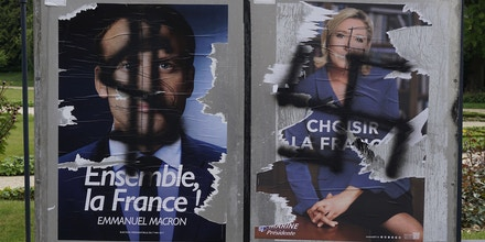 A photo taken in Rennes on May 5, 2017 shows election campaign posters for French presidential election candidate for the En Marche ! movement Emmanuel Macron (L) spray painted with a dollar sign, and French presidential election candidate for the far-right Front National Marine Le Pen spray painted with a swastika. / AFP PHOTO / DAMIEN MEYER        (Photo credit should read DAMIEN MEYER/AFP/Getty Images)
