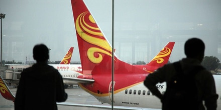 Passengers look on June 12, 2014 at planes belonging to China's Hainan Airlines at the gate at Haikou airport in south China's Hainan province. Hainan Airlines is finalizing a deal to buy 50 fuel-efficient 737 MAX passenger planes from US aircraft maker Boeing, the two companies announced on July 16. AFP PHOTO / STRINGER - CHINA OUT - (Photo credit should read -/AFP/Getty Images)