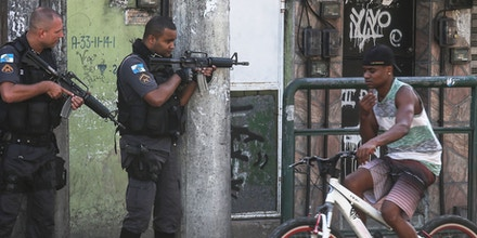 RIO DE JANEIRO, BRAZIL - NOVEMBER 20:  Military Police (PM) officers hold their weapons as a young man bikes past in the Cidade de Deus 'City of God' favela community during an ongoing police operation on November 20, 2016 in Rio de Janeiro, Brazil. Seven local young men were found killed in the area today following a prolonged firefight between police and suspected gang members. In addition, four police officers were killed yesterday when their support helicopter crashed nearby during the firefight. According to preliminary indications the helicopter was likely not shot down.  (Photo by Mario Tama/Getty Images)