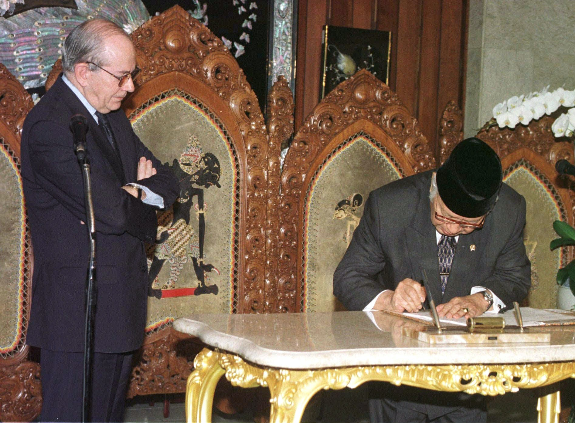 International Monetary Fund (IMF) Managing Director Michel Camdessus, left, looks on as Indonesian President Suharto signs the new IMF deal at Cendana Residence in Jakarta Thursday, Jan. 15, 1998. Bowing to international pressure for reform, President Suharto signed a new deal with the IMF aimed at boosting Indonesia's troubled economy. (AP Photo/Muchtar Zakaria)
