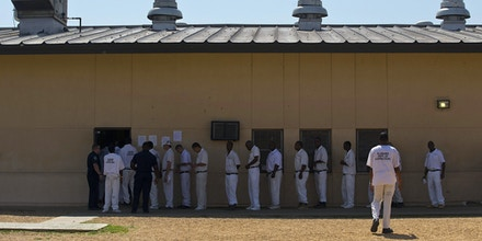 FILE - In this June 18, 2015, file photo, prisoners stand in a crowded lunch line during a prison tour at Elmore Correctional Facility in Elmore, Ala. Alabama is trying to stave off federal intervention in its overcrowded prison system with a reform package approved this spring that includes a bond issue for additional prison space and a new law making sweeping changes to sentencing and probation standards.  (AP Photo/Brynn Anderson, File)