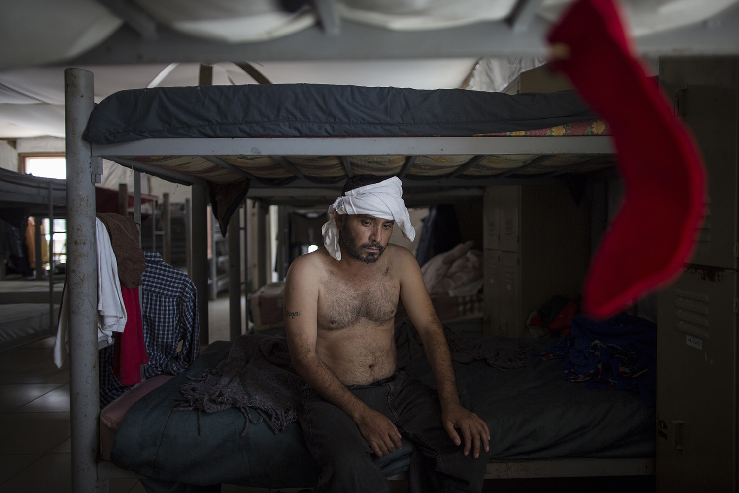 "Delfino Luis Trevino, with his head bandaged, rests on a bunk bed at the ""Senda de Vida"" migrant shelter in Reynosa, Mexico, Wednesday, March 22, 2017. Trevino, from Veracruz, Mexico, said he was beaten one week ago by ""polleros,"" the Spanish name for human traffickers on the border, because he tried to cross to McAllen, Texas without hiring them. He said they where charging $500 dollars. (AP Photo/Rodrigo Abd)"