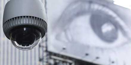 A security camera is mounted on the side of a building overlooking an intersection in midtown Manhattan, Wednesday, July 31, 2013 in New York. In the background is a billboard of a human eye. (AP Photo/Mark Lennihan)