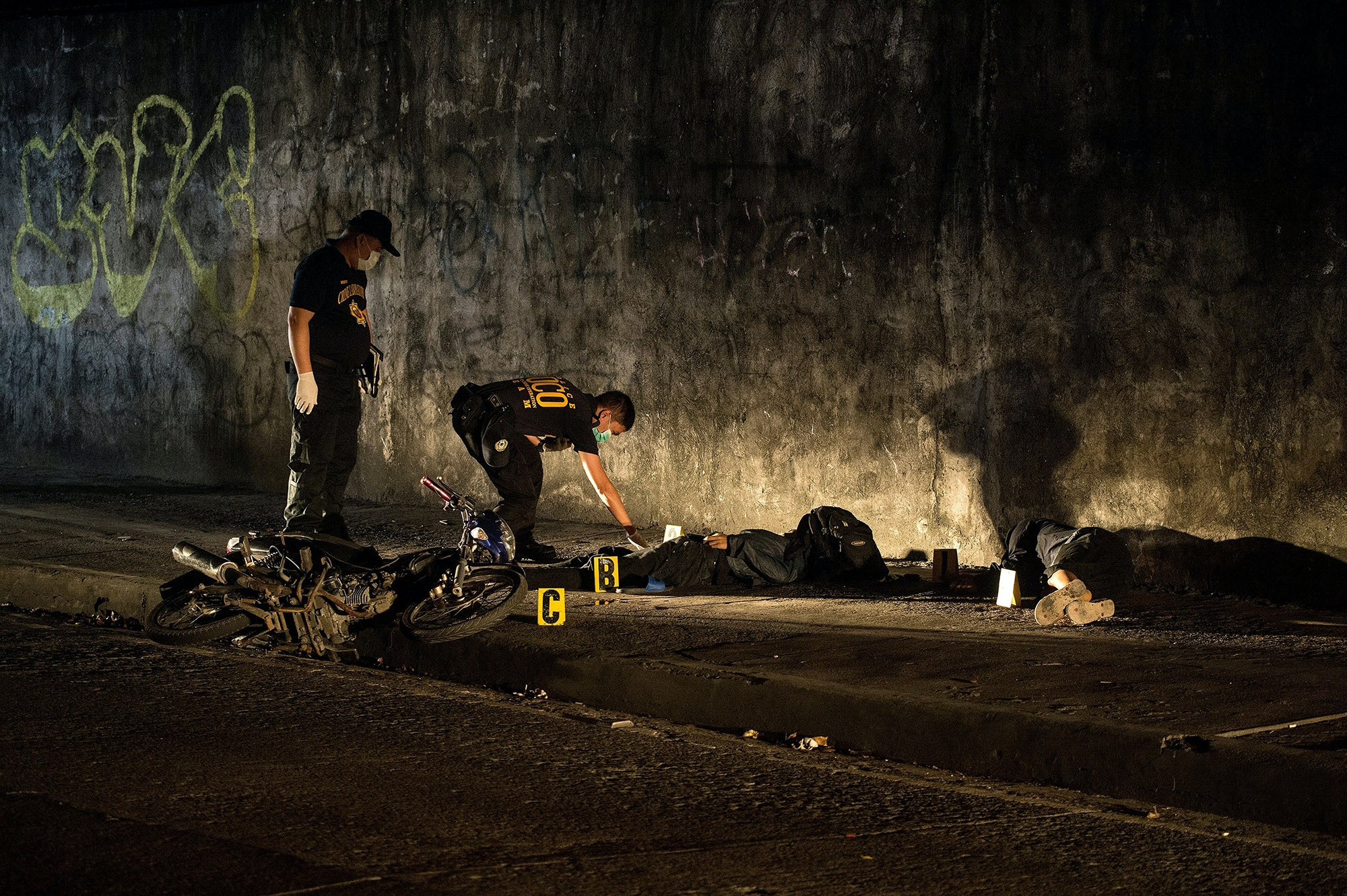 "This picture taken on February 8, 2017 shows a member of a ""Scene of the Crime Operatives (SOCO)"" team investigating the crime scene where two alleged robbers were killed after a gun fight with police in Manila.<br /><br /><br /><br /><br /><br /> Shadowy assassins have killed scores of poor victims in the Philippines after President Rodrigo Duterte officially ordered police to withdraw from his deadly drug war, a rights monitor said on February 17. / AFP / NOEL CELIS        (Photo credit should read NOEL CELIS/AFP/Getty Images)"