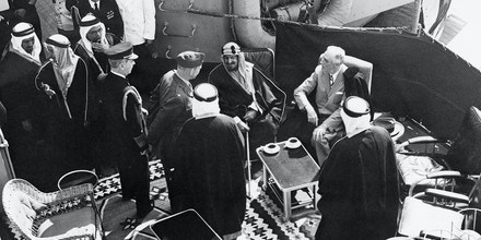(Original Caption) 2/20/1945-Alexandria, Egypt- A view of the scene aboard an American warship at Great Bitter Lake, Egypt, when President Roosevelt Conferred with King Ibn Saud of Saudi Arabia. The King and the President are seated. Admiral Leahy stands behind and unidentified U.S. Colonel in the center. In the background are aides to the visiting King. This meeting took place while the President was enroute home from the Yalta Conference.