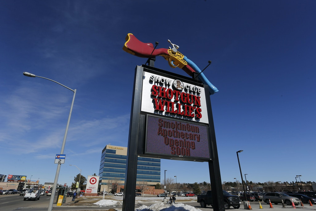 In this Feb. 10, 2016 photo, a large roadside sign marks the entrance of longtime strip club Shotgun Willie's, and Smoking Gun Apothecary, the new marijuana dispensary, in Glendale, Colo.   Smokin Gun Apothecary is on a site formerly occupied by the Denver area's best known strip club, Shotgun Willie's. The strip club hasn't gone away, it's moved just across the parking lot. Both businesses have the same owner, who envisions pot shoppers getting discounted drinks at the strip club and is outfitting the roof of the pot shop for a future lounge in case Colorado changes its law banning on-site marijuana consumption.(AP Photo/Brennan Linsley)