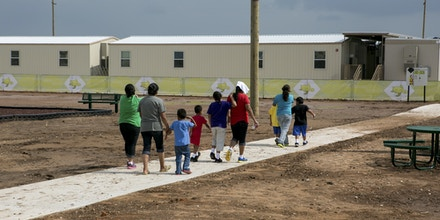 DILLEY, TEXAS - May 14, 2015: Residents walk across the grounds at The South Texas Family Residential Center. The South Texas Family Residential Center in Dilley, Texas was built in December 2014 to host up to 2,400 undocumented women and children who are seeking asylum. The Dilley facility is the largest of its kind, and while residents may move freely from building to building, they are not permitted to leave the grounds.