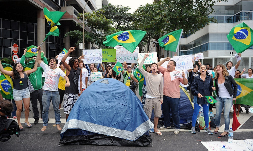 Protesters camping, since last night, in front of the residence of Rio de Janeiro's governor Sergio Cabral, in Leblon, Rio de Janeiro, shout slogans while blocking the street on June 22, 2013. Brazil girded for more street protests Saturday despite President Dilma Rousseff's conciliatory remarks pledging to improve public services and fight corruption, while warning against further violence. Her speech came a day after more than one million people marched in cities across the country to slam the huge cost of hosting next June's World Cup, put at some 15 billion dollars, while public services such as schools and hospitals are lacking.   AFP PHOTO / TASSO MARCLEO        (Photo credit should read TASSO MARCELO/AFP/Getty Images)