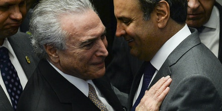 President Michel Temer (L) speaks with senator Aecio Neves before taking office before the plenary of the Brazilian Senate in Brasilia, on August 31, 2016. Brazil's Dilma Rousseff was stripped of the country's presidency in an impeachment vote Wednesday and replaced by her bitter rival Michel Temer, shifting Latin America's biggest economy sharply to the right. / AFP PHOTO / ANDRESSA ANHOLETE (Photo credit should read ANDRESSA ANHOLETE/AFP/Getty Images)