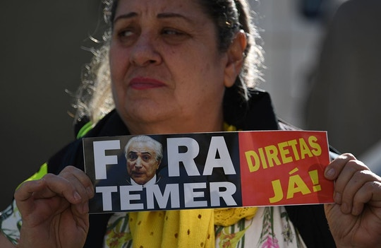 A supporter of former Brazilian president Dilma Rousseff protests against President Michel Temer during a campaign rally for Jandira Feghali, Communist Party candidate for mayor of Rio de Janeiro, where Rousseff gave a speech in Rio de Janeiro on September 21, 2016. / AFP / VANDERLEI ALMEIDA        (Photo credit should read VANDERLEI ALMEIDA/AFP/Getty Images)