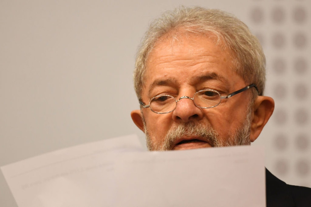 "Former Brazilian President (2003-2010) Luiz Inacio Lula da Silva reads during a seminar on ""Strategies for the Brazilian Economy"" promoted by the Workers' Party in Brasilia, on April 24, 2017.<br /><br /><br /><br /> Lula da Silva, who faces allegations of involvement in the Odebratch scandal, had his graft probe testimony postponed to May 10. / AFP PHOTO / EVARISTO SA        (Photo credit should read EVARISTO SA/AFP/Getty Images)"
