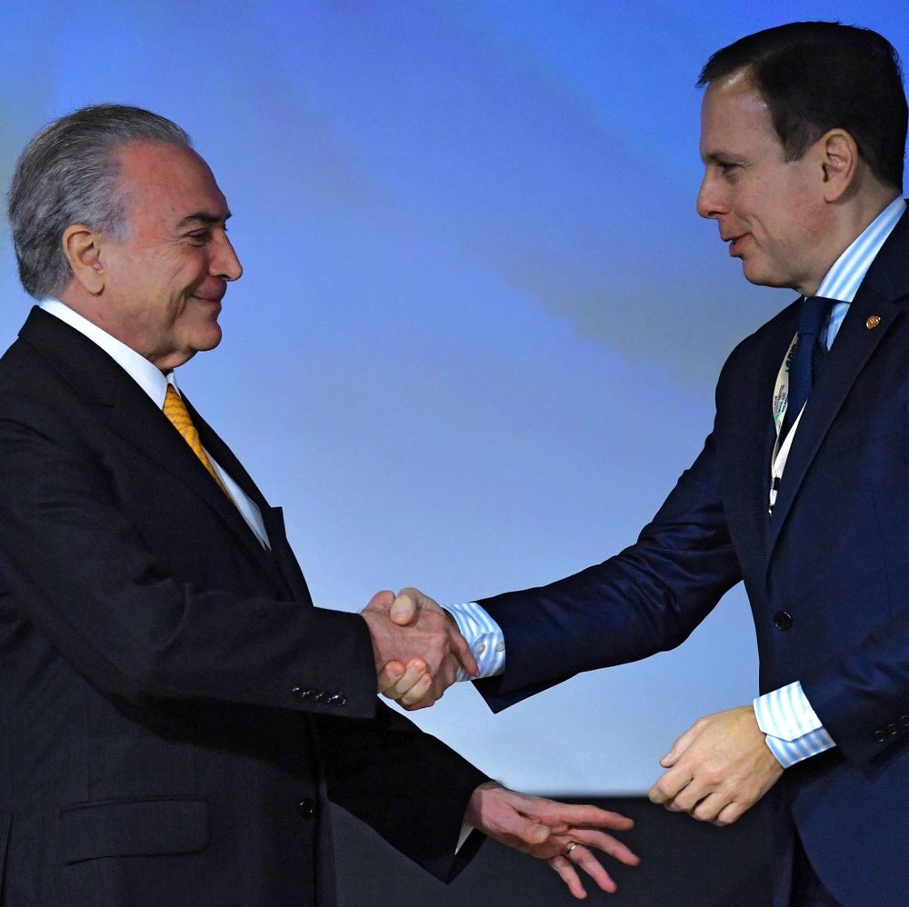 Sao Paulo's mayor Joao Doria (R) shakes hands with Brazilian President Michel Temer, during an Investment Forum in Sao Paulo, Brazil on May 30, 2017. / AFP PHOTO / NELSON ALMEIDA        (Photo credit should read NELSON ALMEIDA/AFP/Getty Images)