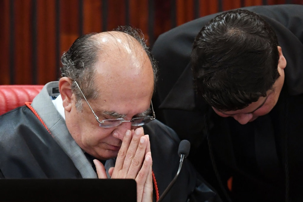 Supreme Electoral Court (TSE) President Judge Gilmar Mendes (L), gestures during a session examining whether the 2014 reelection of president Dilma Rousseff and her then-vice president Temer should be invalidated because of corrupt campaign funding, in Brasilia, on June 7, 2017.<br /><br /> Judges on Brazil's electoral court were expected to start voting Wednesday in a case that could topple scandal-tainted President Michel Temer. If the court votes to scrap the election result, Temer -- who took over only last year when Rousseff was impeached -- would himself risk losing his office.<br /><br />  / AFP PHOTO / EVARISTO SA        (Photo credit should read EVARISTO SA/AFP/Getty Images)