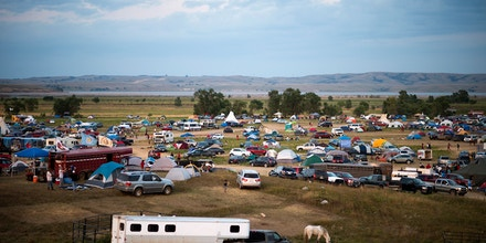 People gather at an encampment by the Missouri River, where hundreds of people have gathered to join the Standing Rock Sioux Tribe's protest against the construction of the Dakota Access Pipe (DAPL), near Cannon Ball, North Dakota, on September 3, 2016.The Indian reservation in North Dakota is the site of the largest gathering of Native Americans in more than 100 years. Indigenous people from across the US are living in camps on the Standing Rock reservation as they protest the construction of the new oil pipeline which they fear will destroy their water supply. / AFP / Robyn BECK (Photo credit should read ROBYN BECK/AFP/Getty Images)