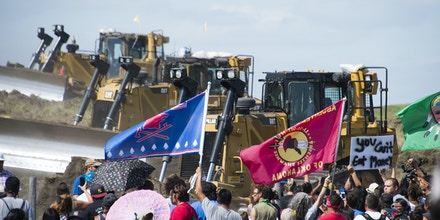 Members of the Standing Rock Sioux Tribe and their supporters opposed to the Dakota Access Pipeline (DAPL) confront bulldozers working on the new oil pipeline in an effort to make them stop on September 3, 2016, near Cannon Ball, North Dakota.Private security guards used pepper sprayed and attack dogs to attempt to repell the protestors but eventually the bulldozers and the security guards retreated. / AFP / Robyn BECK (Photo credit should read ROBYN BECK/AFP/Getty Images)