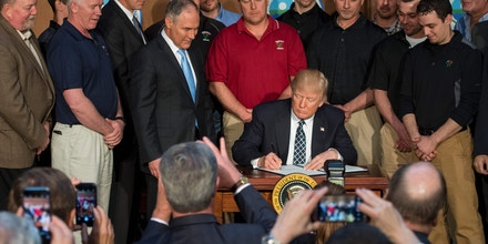 TOPSHOT - Surrounded by miners from Rosebud Mining, US President Donald Trump (C) signs he Energy Independence Executive Order at the Environmental Protection Agency (EPA) Headquarters in Washington, DC, March 28, 2017.President Donald Trump claimed an end to the