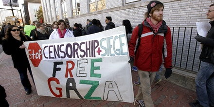 Ryan Branagan carries a sign during a protest in support of Palestine after a Northeastern University student organization, Students for Justice in Palestine was