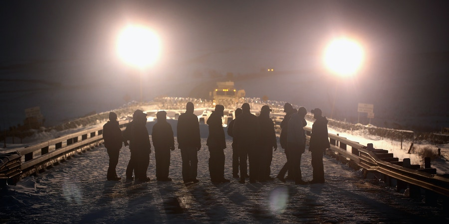 CANNON BALL, ND - DECEMBER 01:  Military veterans confront police guarding a bridge near Oceti Sakowin Camp on the edge of the Standing Rock Sioux Reservation on December 1, 2016 outside Cannon Ball, North Dakota. Native Americans and activists from around the country have been gathering at the camp for several months trying to halt the construction of the Dakota Access Pipeline. The proposed 1,172-mile-long pipeline would transport oil from the North Dakota Bakken region through South Dakota, Iowa and into Illinois.  (Photo by Scott Olson/Getty Images)
