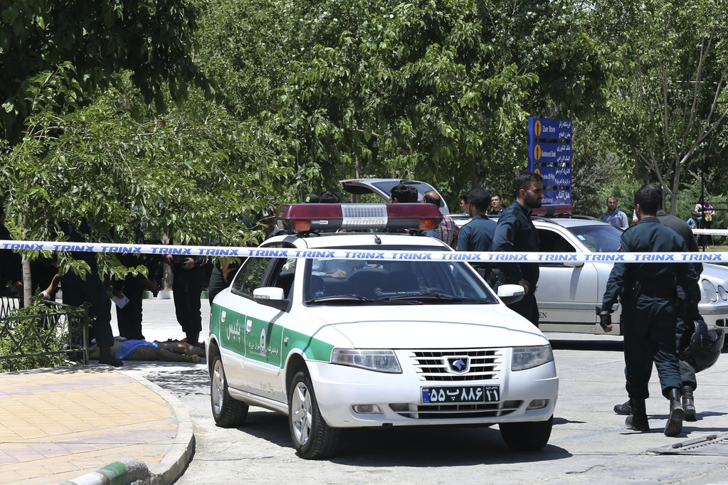 The body at background left, lies on the ground while police control the scene at the shrine of late Iranian revolutionary founder Ayatollah Khomeini, just outside Tehran, Iran, Wednesday, June 7, 2017. Several attackers stormed into Iran's parliament and a suicide bomber targeted the shrine of Ayatollah Ruhollah Khomeini on Wednesday, killing a security guard and wounding 12 other people in rare twin attacks, with the shooting at the legislature still underway. (AP Photo/Ebrahim Noroozi)