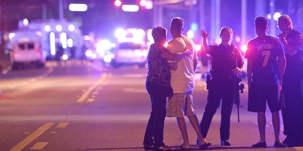 FILE - In this Sunday, June 12, 2016 file photo, Orlando Police officers direct family members away from a fatal shooting at Pulse Orlando nightclub in Orlando, Fla. With news that Omar Mateen killed dozens of people in a gay nightclub in Florida and was born to Afghan immigrant parents, the Afghan-American community is expressing horror, sorrow and disbelief that one of their own could commit the worst mass shooting in modern U.S. history. (AP Photo/Phelan M. Ebenhack, File)