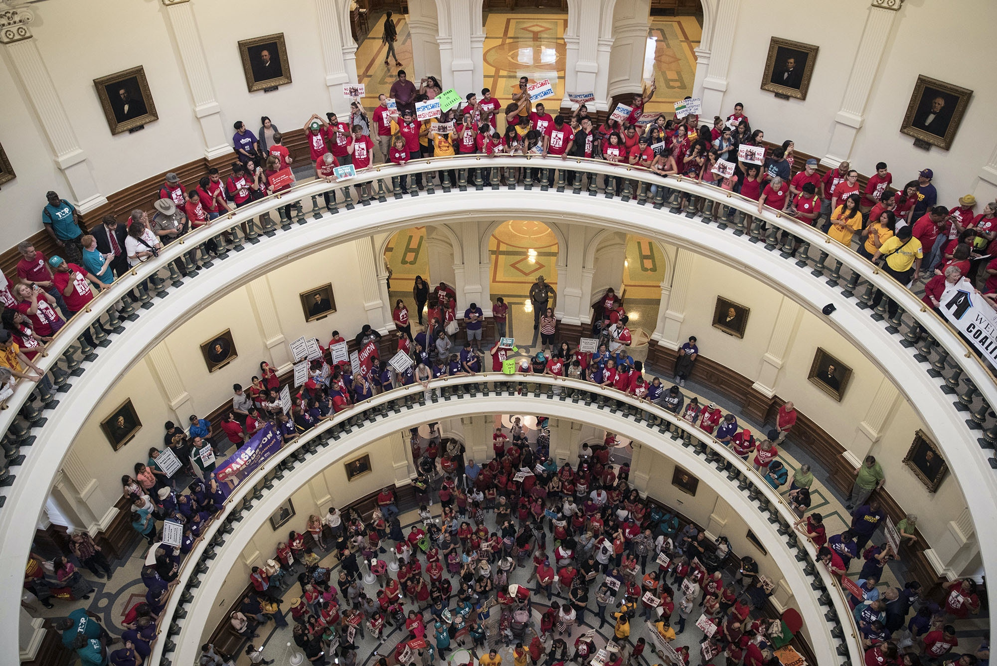 Hundreds of protesters line the balconies of the state Capitol rotunda in Austin on Monday, May 29, 2017, the last day of the legislative session, to protest Senate Bill 4. legislation already passed by Texas Gov. Greg Abbott that compels local police to enforce federal immigration law. (Ricardo Brazziell/Austin American-Statesman via AP)