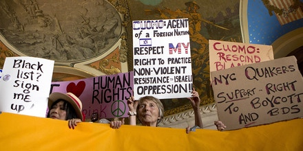 People hold signs during a rally in the War Room at the state Capitol on Wednesday, June 15, 2016, in Albany, N.Y. Critics of Israel's treatment of Palestinians protested Gov. Andrew Cuomo's executive order prohibiting state investments in any company that supports a boycott of Israel. (AP Photo/Mike Groll)