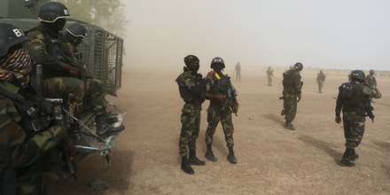 Cameroonian soldiers from the Rapid Intervention Brigade stand guard amidst dust kicked up by a helicopter in Kolofata, Cameroon, March 16, 2016. The brigade is known by its French acronym BIR. After watching its influence spread during a six-year campaign that has killed around 15,000 people according to the U.S. military, Nigeria has now united with its neighbours to stamp out Boko Haram. An 8,700-strong regional force of troops from Benin, Cameroon, Chad, Niger, and Nigeria is seeking to finish the job. Outside Nigeria, Cameroon has been hardest hit by Boko Haram, which now operates out of bases in the Mandara Mountains, Sambisa Forest and Lake Chad.  REUTERS/Joe Penney   SEARCH