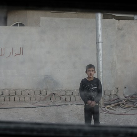 A young boy stares at the photographer through the window of an Iraqi army Humvee in the Karkukli neighborhood of Mosul, Iraq on Nov. 17, 2016.