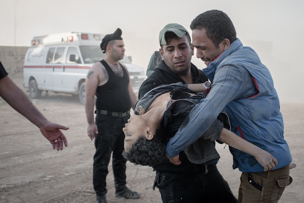 A man hands his younger brother, killed by an IED, to a medic at a field clinic in the Samah neighborhood of Mosul, Iraq on Nov. 18, 2016.