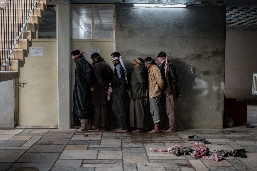Newly displaced civilians from Hawija wait outside an interrogation room in a base run by Asayish, Kurdish Regional Government security forces, in Dibis, Iraq on Dec. 12, 2016.