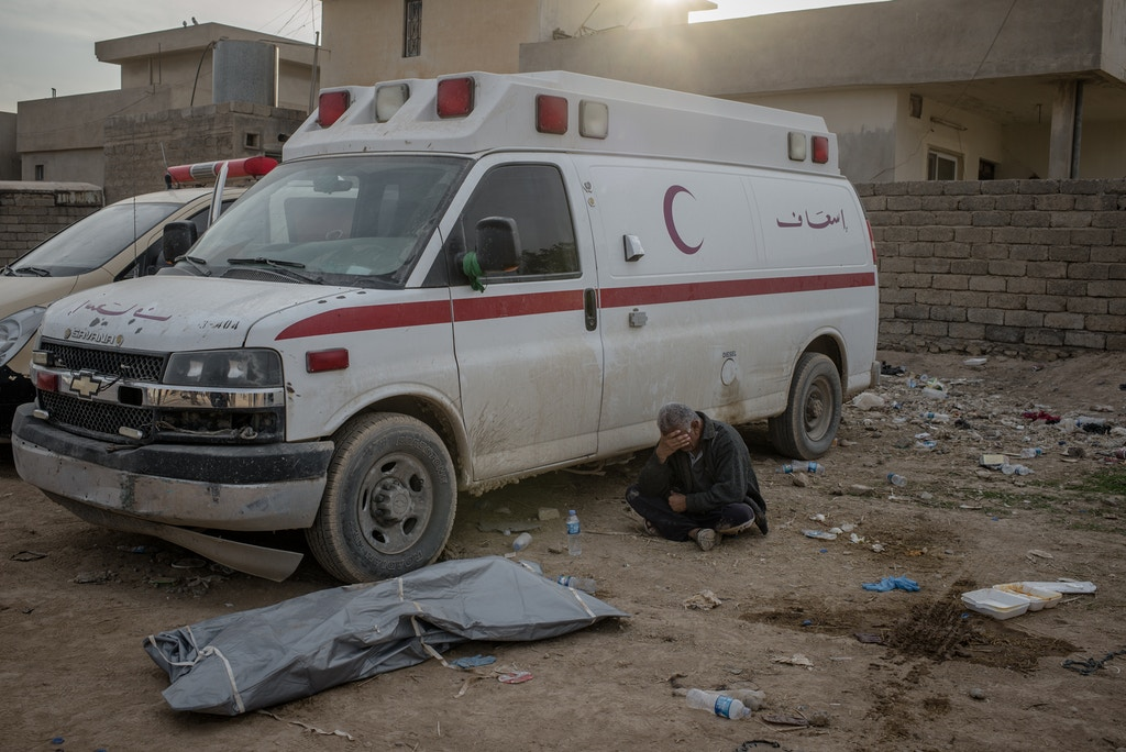 Matham Tarek's father cries near his son's body at a field clinic in the Samah neighborhood of Mosul, Iraq on Nov. 13, 2016. He was killed by a mortar attack.