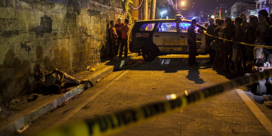 A dead body is revealed as police shine their flashlights during an investigation of a crime scene in Manadaluyong city . The killing was allegedly perpetrated by masked vigilantes who hogtied the victim before he was shot.copyright 2017 Luis Liwanag