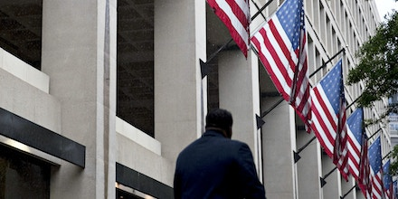 A pedestrian walks past American Flags hanging on display outside the Federal Bureau of Investigation (FBI) headquarters in Washington, D.C., U.S., on Thursday, May 11, 2017. President Donald Trump this week fired FBI Director James Comey amid the agency's investigation of Russian interference in last years election, saying the bureau needed new leadership to restore public trust and confidence. Photographer: Andrew Harrer/Bloomberg via Getty Images