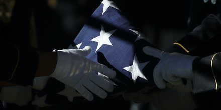 ARLINGTON, VA - DECEMBER 05:  The American flag that covered the casket of U.S Army Staff Sgt. James F. Moriarty is folded by members of the burial team during the soldier's burial service at Arlington National Cemetery December 5, 2016 in Arlington, Virginia. Moriarty and two other members of the U.S. Special Forces were killed during an attack outside a military base in Jordan on November 4, 2016.  (Photo by Win McNamee/Getty Images)