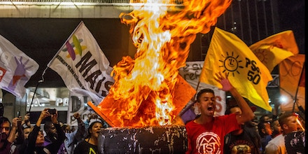 Members of Brazil's Homeless Workers' Movement (MTST) shout slogans in front of the Sao Paulo Industry Federation (FIESP) building during a protest against Brazil President Michel Temer's proposed changes to labour and pension laws in Sao Paulo, Brazil, July 10, 2017 (Photo by Cris Faga/NurPhoto via Getty Images)