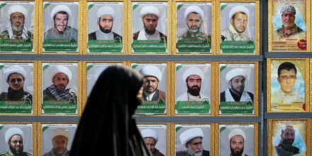 An Iraqi Shiite Muslim pilgrim walks past a billboard bearing portraits of popular mobilisation units members, who died fighting against the Islamic State (IS) group, as she heads towards the shrine of Imam Musa al-Kadhim in Baghdads northern district of Kadhimiya on April 21, 2017, to mark the anniversary of the death of the religious figure. / AFP PHOTO / AHMAD AL-RUBAYE        (Photo credit should read AHMAD AL-RUBAYE/AFP/Getty Images)