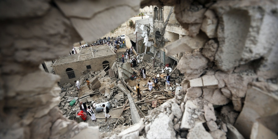 Yemenis stand on the rubble of houses destroyed in a suspected Saudi-led coalition air strike in Sanaa on June 9, 2017.Four civilians, including two teenagers, died