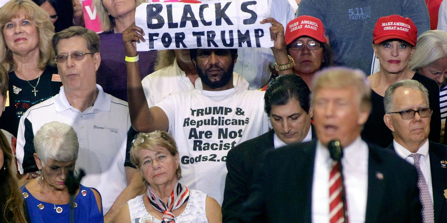 """b82a4134 Man Waving """"Blacks for Trump"""" Sign at President's Rally has Bizarre Beliefs  about Race War"""