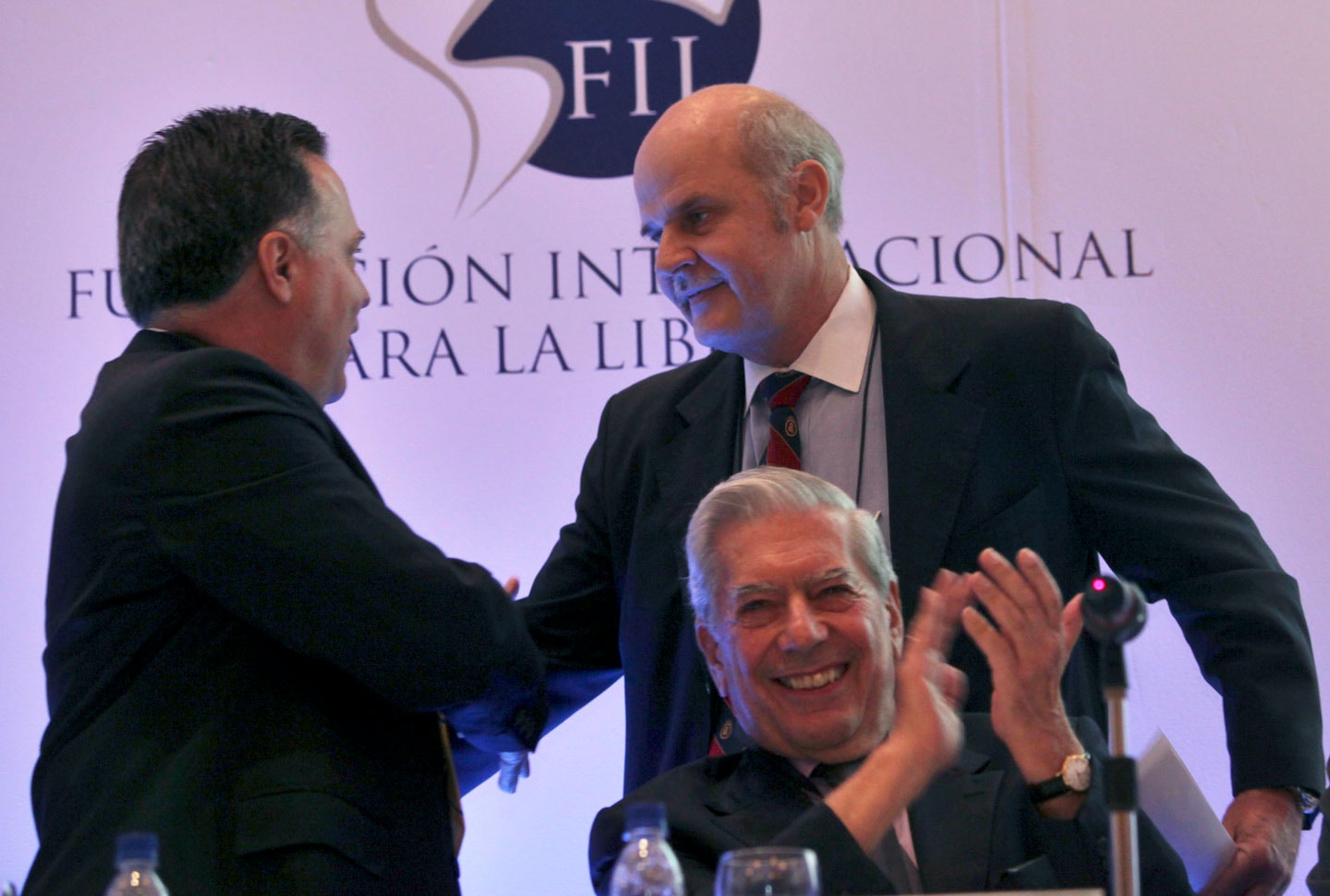 "Alejandro Chafuen, of the Atlas Economic Research Foundation, back right, shakes hands with Rafael Alonzo, of Venezuela's Freedom Center for  Economic Studies, CEDICE, left, as Peruvian writer Mario Vargas Llosa applauds during the opening of the ""Freedom and Democracy"" international  forum in Caracas, Thursday, May 28, 2009.(AP Photo/Ariana Cubillos)"