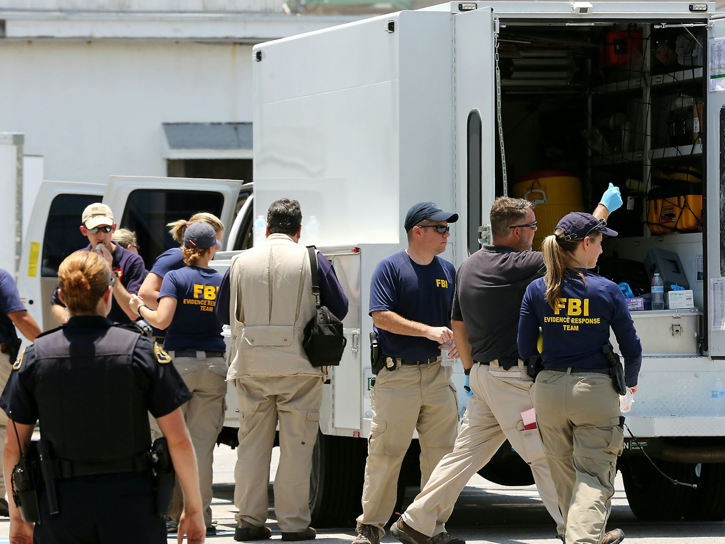 In this photo taken on Monday, July 27, 2015, federal agents and Key West Police gather in a restaurant parking lot in Key West, Fla. A man described by the FBI as an Islamic State sympathizer who hoped to mount attacks on U.S. soil was charged Tuesday with plotting to detonate a nail-filled backpack bomb on a Florida beach. (Rob O'Neal/The Key West Citizen via AP)  MIAMI OUT; MANDATORY CREDIT